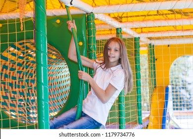 Beautiful little girl is playing in the children's playroom.