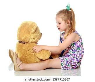 Beautiful little girl is playing doctor. She listens through a phonendoscope of a teddy bear. The concept of play and family happiness.