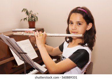 beautiful little girl playing the flute at the music school