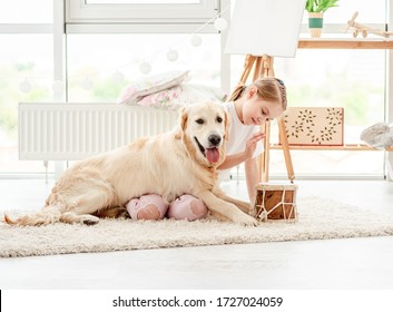 Beautiful little girl playing music with lovely dog indoors