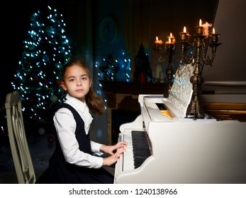Beautiful little girl is playing on a white piano in a dark room by candlelight. The concept of Christmas and New Year, family happiness.