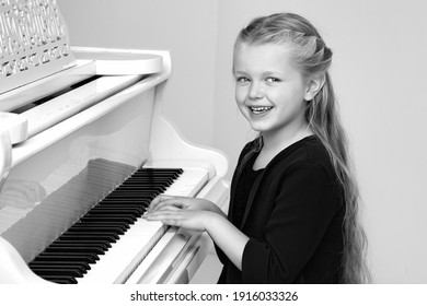 Beautiful little girl playing on white grand piano