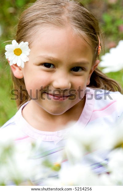 beautiful little girl portrait with flowers in front of her and on her ear