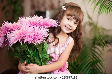 Beautiful little girl posing with a large bouquet of flowers in a luxurious pink dress at home.