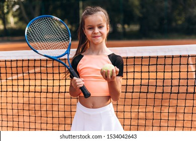 Beautiful little girl posing on tennis court with racket and tennis ball