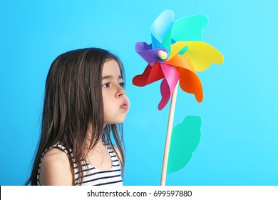 Beautiful little girl with rainbow whirligig on blue background