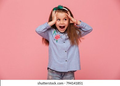 Beautiful little girl reacting emotionally grabbing head with both hands, being delighted and shocked over pink background