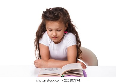 Beautiful little girl reading a book while sitting at table on white background