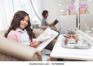 Beautiful little girl is reading a magazine in a beauty salon. She smiles and looks into the magazine with enthusiasm. A dark-haired girl in a pink blouse is sitting in the beauty salon chair.