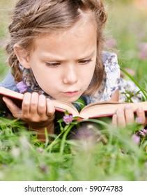 Beautiful little girl reads book, lying on green lawn.