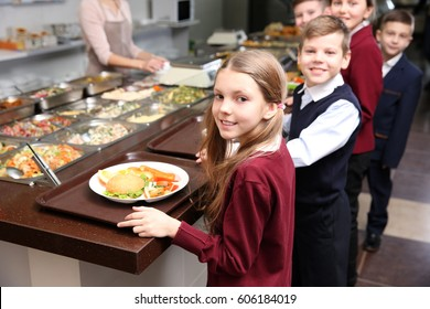 Beautiful little girl receiving food in school cafeteria