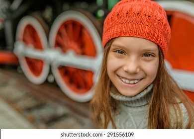 Beautiful little girl in a red cap near the old steam locomotive.