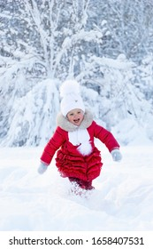 A beautiful little girl in a red coat and white hat with a scarf runs along a snowy path in a winter park. Smile and children's joy on the face. Enjoyment in the winter season. Great holidays. Snow