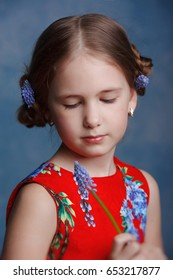 Beautiful little girl in a red dress in the Studio on a blue background.