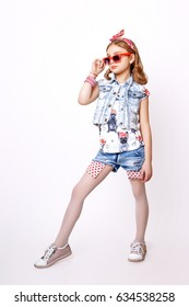 beautiful little girl with red lips on a white background. Studio photo. Dressed in a glasses, denim vest and jeans shorts.