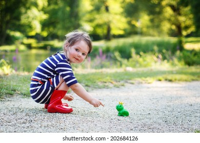 Beautiful little girl in red rain boots playing with rubber frog. Outdoors
