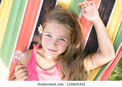 beautiful little girl is resting on a hammock with flowers in hands