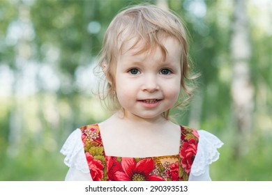 Beautiful little girl in russian traditional clothes in nature.Little cute girl in Russian national clothes.Traditional Russian folk costume.Portrait of a cute little girl outside