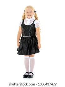 Beautiful little girl in a school uniform on a white background. The concept of style and fashion, advertising and education. Isolated.