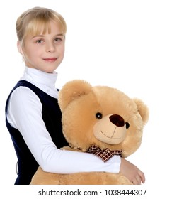 Beautiful little girl schoolgirl embraces with a teddy bear. The concept of a happy childhood, children's emotions.