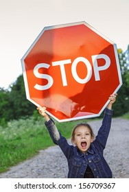 "Beautiful little girl screaming and holding red sign ""STOP""."