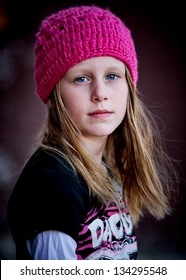 Beautiful little girl with serious face wearing pink knit hat and looking at camera