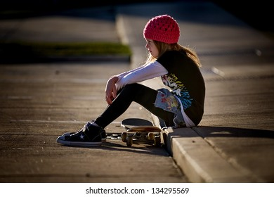 Beautiful little girl with serious face wearing pink knit hat and sitting on curb with her skateboard, looking off into the distance