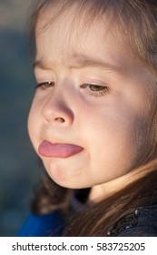 beautiful little girl showing tongue