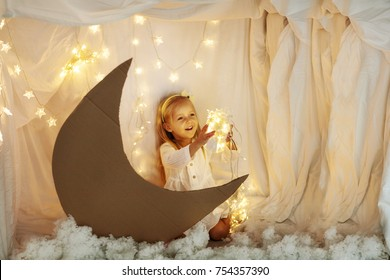 beautiful little girl sits in the studio with a decor of the moon, stars and clouds and holds in her hands a sparkling garland of golden color