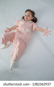 The beautiful little girl was sitting on the floor in her pajamas, white background