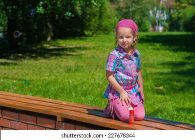 Beautiful little girl sitting on her knees on a bench in the park