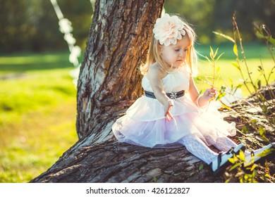 beautiful little girl sitting on a tree
