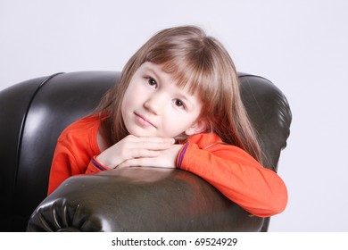 Beautiful little girl sitting on a leather chair