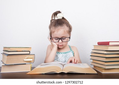 Beautiful little girl is sitting at the table with a bunch of books