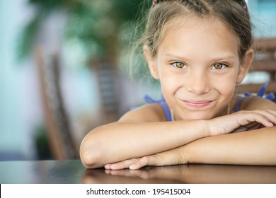 Beautiful little girl sitting at table and smiling.