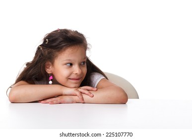 beautiful little girl sitting at the table and looking away, isolated on white background. emotions concept