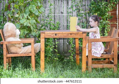 Beautiful little girl sitting with Teddy bear on a wooden table outside in backyard playground, reading to her little plush friend