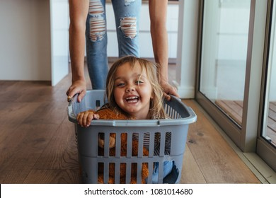 Beautiful little girl sitting in a washing basket being pushed by her mother. Cute little girl and her mother playing while doing laundry at home.