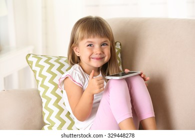 Beautiful little girl  with smart phone sitting on sofa, on home interior background