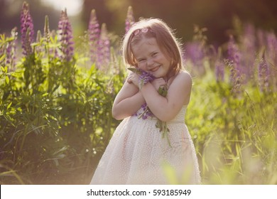 Beautiful little girl smiling and playing with a basket in his hands in a field of purple flowers