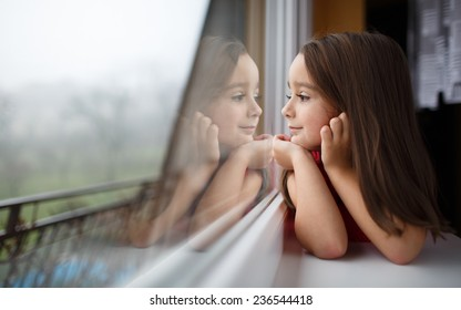 Beautiful little girl smiling and watching out the window. A child looks out the window. Young girl looking from window. Portrait of cheerful kid sits at window.