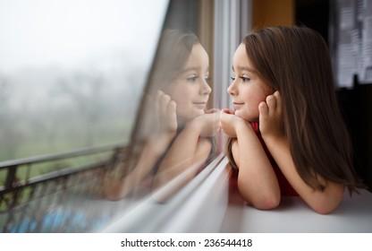 Schönes kleines Mädchen lächelt und sieht aus dem Fenster. Ein Kind schaut aus dem Fenster. Junge Mädchen, die aus dem Fenster schauen. Porträt fröhlicher Kinder sitzt am Fenster.