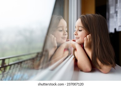 Beautiful little girl smiling and watching out the window. A child looks out the window. Young girl looking from window. Portrait of cheerful kid lies at windowsill.