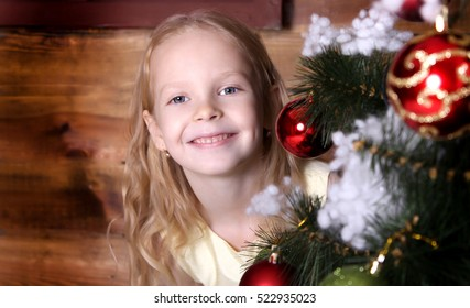 Beautiful little girl standing near the Christmas tree. The girl has blonde hair, she in a yellow dress magical. Girl hangs Christmas ball