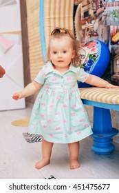 beautiful little girl standing in the nursery