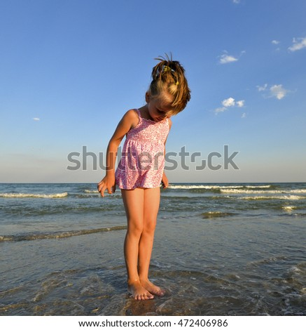 ab75a5e5ccbf Beautiful little girl standing in the water on the beach. Happy baby girl  playing on