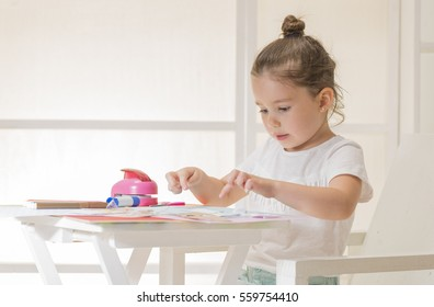Beautiful little girl sticking pieces of paper on the art lesson class. Children education concept. Kids crafts. Learn Study Education School Knowledge Concept