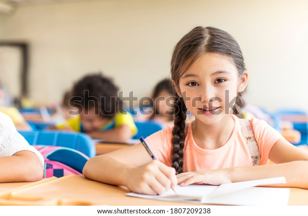 beautiful little girl  studying in the classroom.