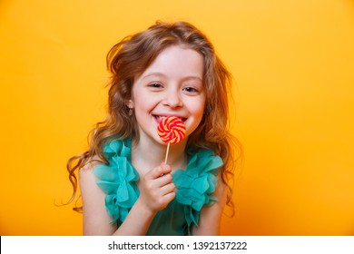 Beautiful little girl with sugar lollipop on yellow background