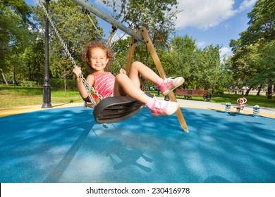 Beautiful little girl swinging on the playground with big nice toothy smile on sunny day